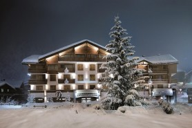 Snowy night time exterior of the Hotel Au Coeur Du Village