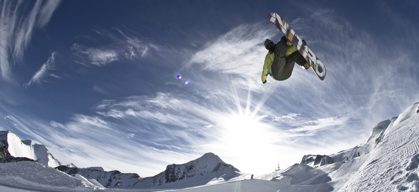 Snowboarder jumping and looking into the camera