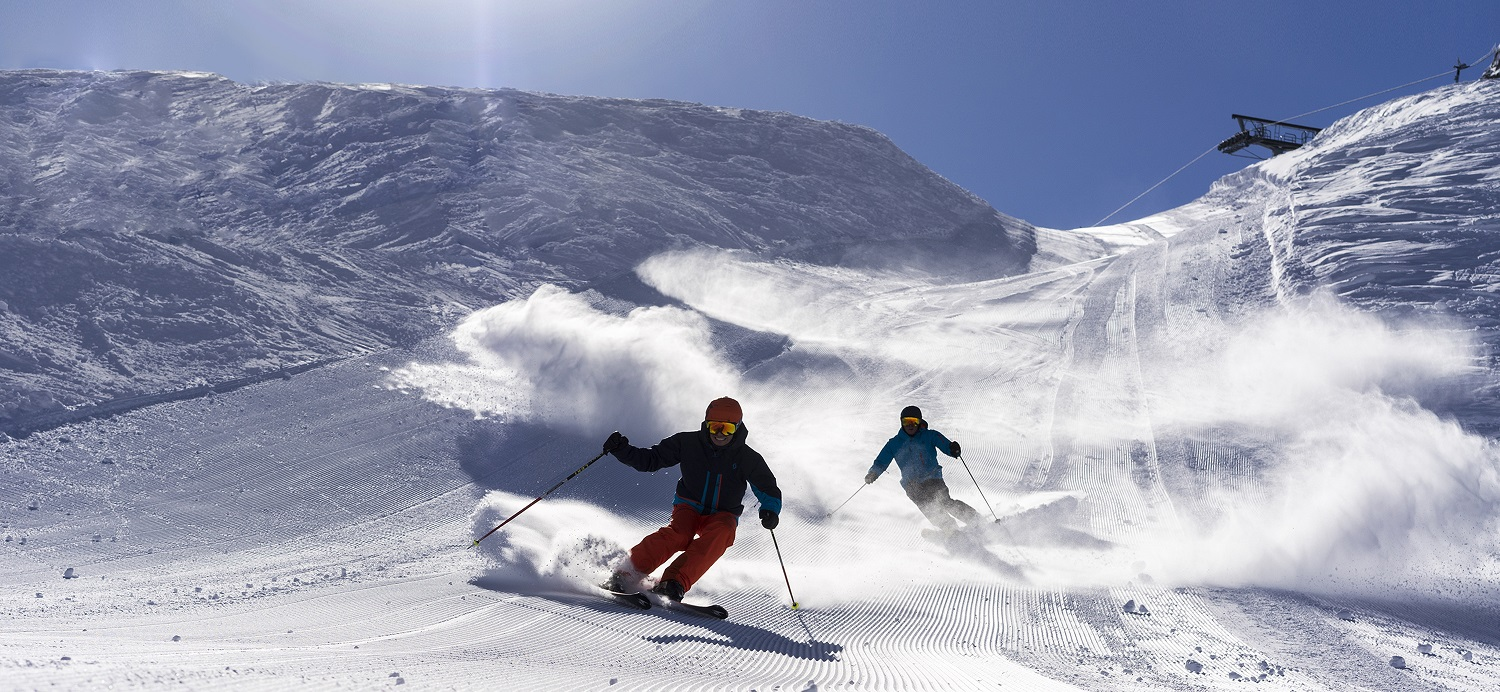 Two Skiers on a steep run