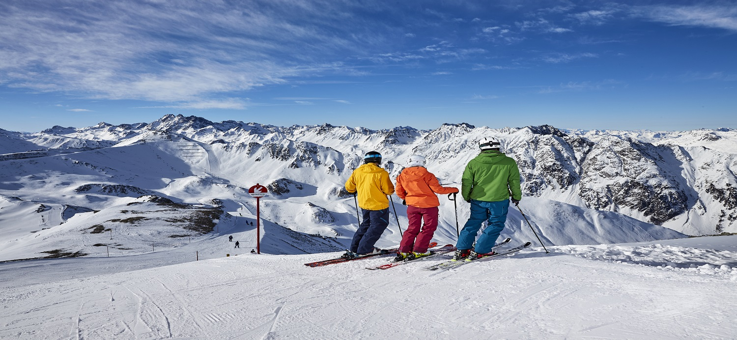 Family of three looking out over the slopes