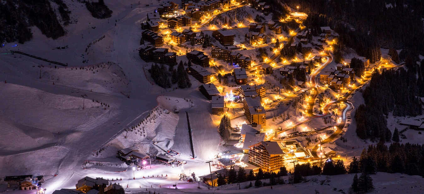 Meribel slopes and hotels lit up at night in the snow