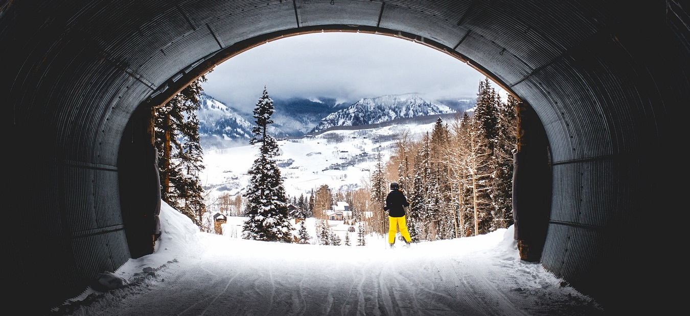 Ski tunnel with mountain views and a skier in yellow