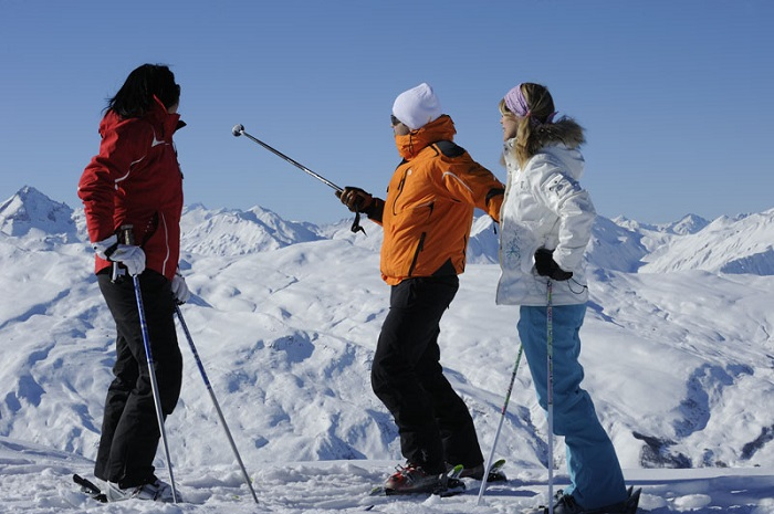 3 skiers looking at a mountain view