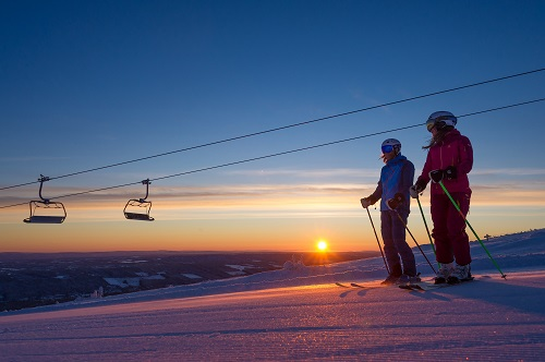 Two skiers watching a cable car and sunset