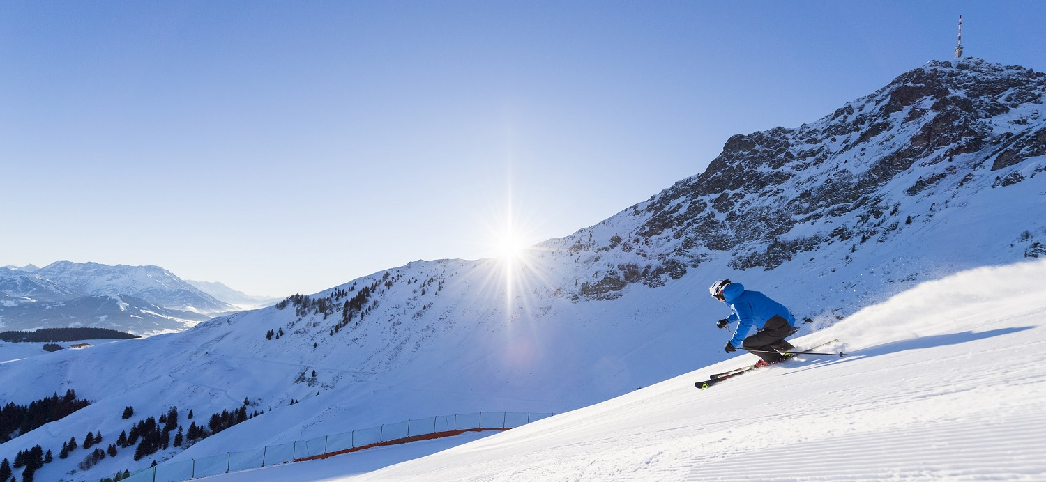 Skier coming down the slopes with sun rising over the mountains behind