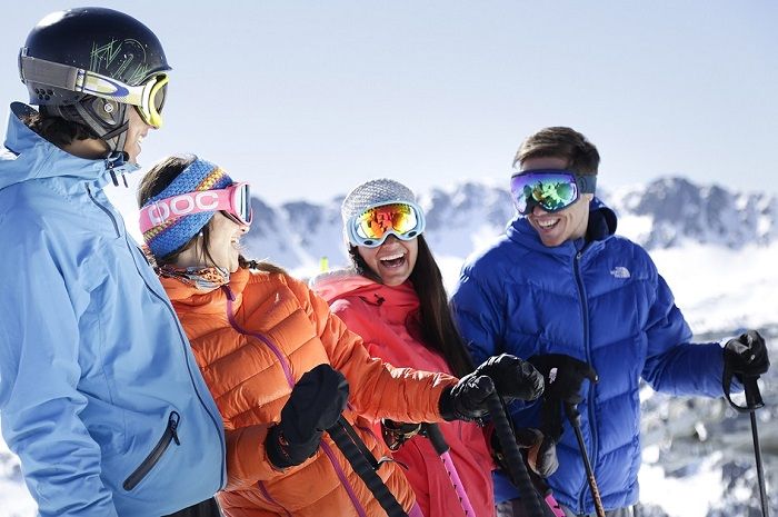 group of four skiers laughing on the slopes
