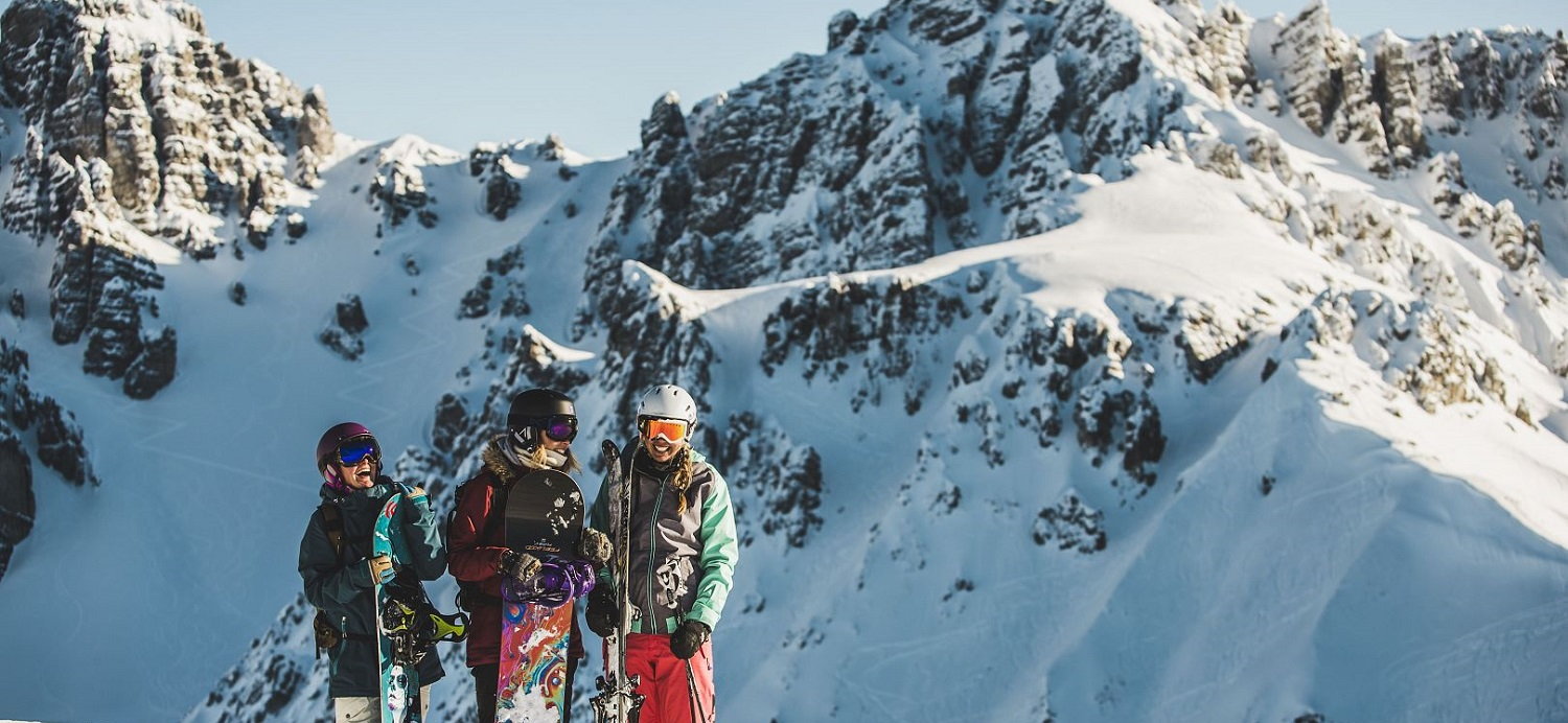 Three snowboarders laughing on the slopes