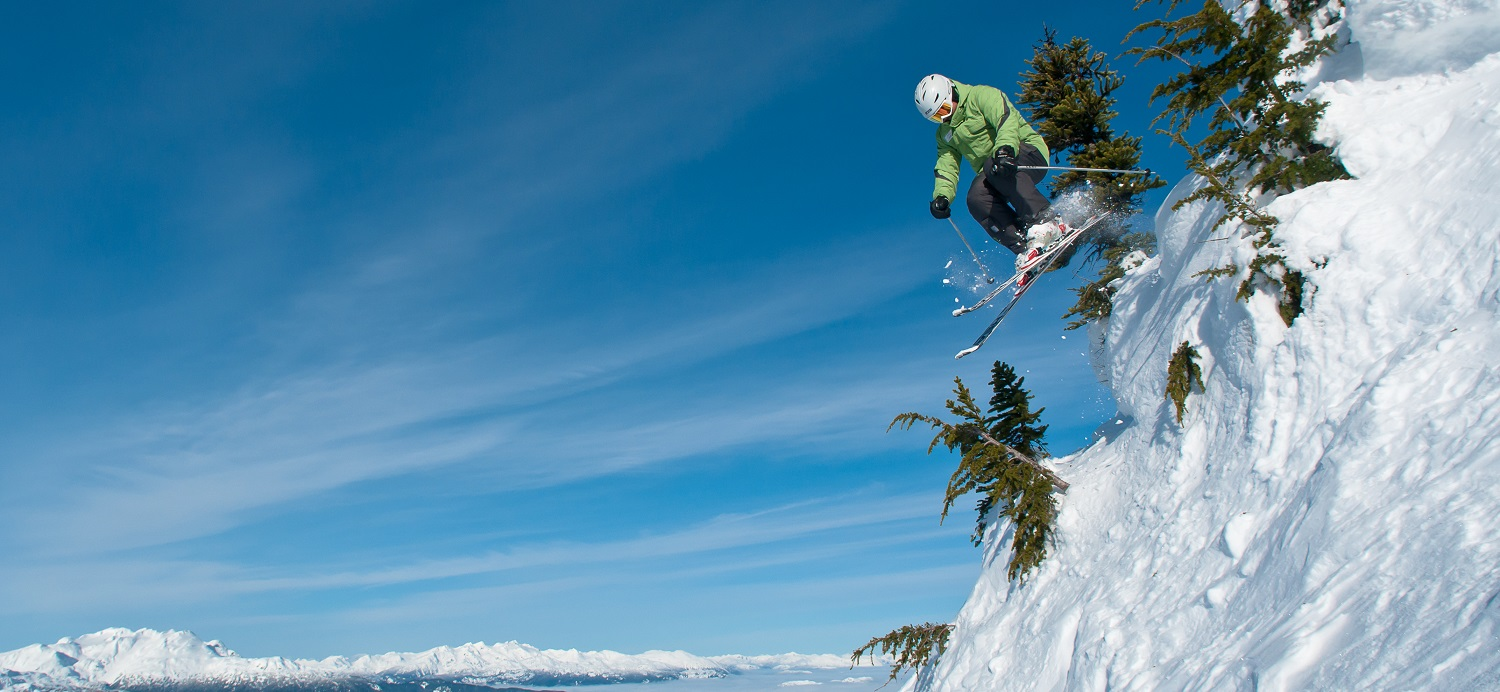 Skier i green jumping out from the trees