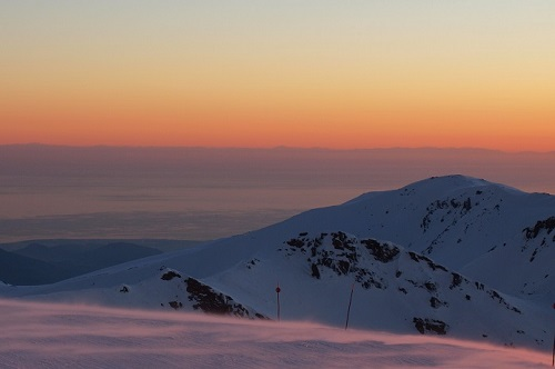 Sunset over partially cloud covered mountains